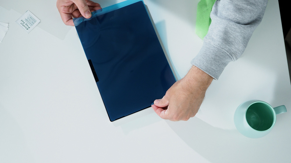 Man holds the Paper-like screen protector above the Surface Pro 7 to show the perfect fit.