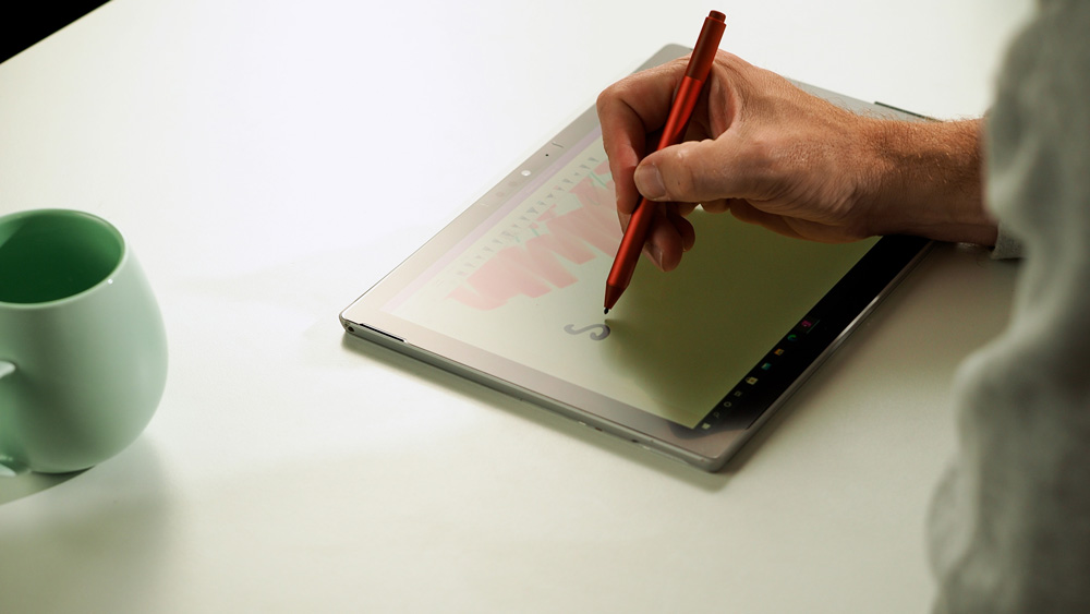 Man's hand holding the poppy red Surface Pro pen as he writes on his Surface Pro 7 with less reflection and more friction, thanks to the new Paper-like screen protector.
