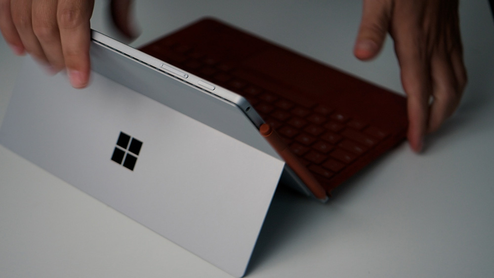 The new unboxed Surface Pro 7+ on the desk with the poppy red keyboard and poppy red Surface pen attached.