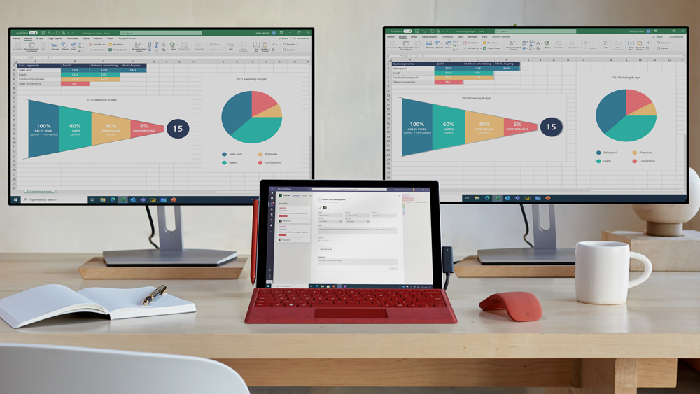 The Surface Pro 7+ on the desk connected to two 4K monitors via the Surface connect dock.