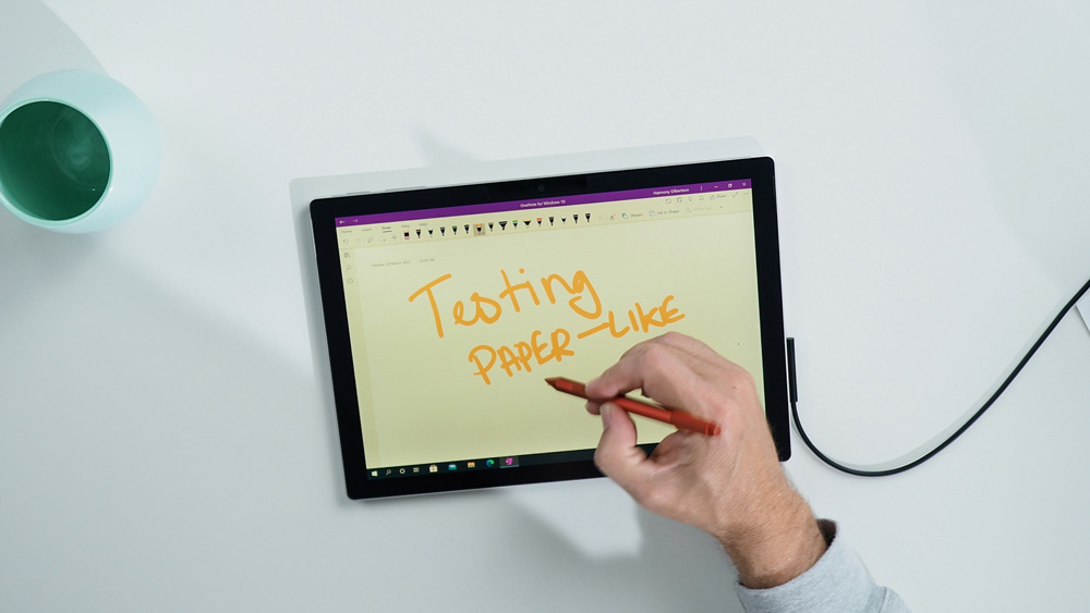 Man's hand writing on the Surface Pro 7 with the poppy red Surface pen, testing the Paper-like screen protector.